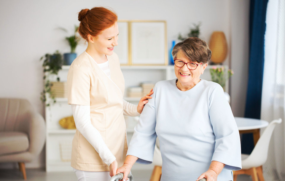 caregiver and and elder woman smiling