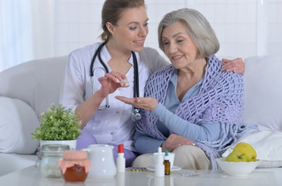 caregiver give a medicine to the elderly